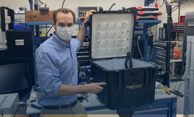 GTRI researcher Robert Harris shows the prototype portable UV disinfection chamber, which was designed to hold at least one face shield along with face masks. (Credit: John Stone)